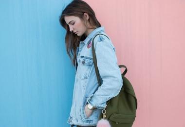 Chica con camiseta vaquera sobre fondo azul y rosa