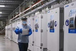 A worker passes a line of freezers holding coronavirus disease (COVID-19) vaccine candidate BNT162b2 at a Pfizer facility in Puurs, Belgium.