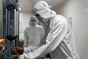 An employee in personal protective equipment (PPE) removes vials of AstraZeneca